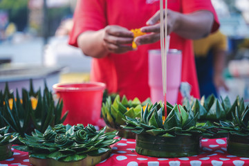 Woman at the market makes traditional decorations for a holiday in Thailand, Loi Kratong of flowers and leaves of candles and incense