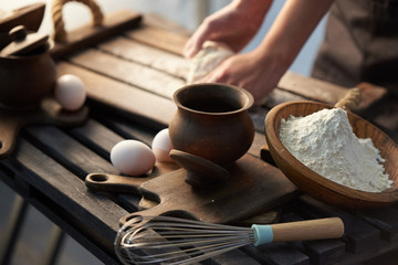 Ingredients for the dough on the table - flour, eggs. Woman kneads the dough with her hands.