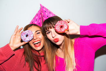 people, friends, teens and friendship concept - happy smiling pretty teenage girls with donuts making faces and having fun over blue background.Picture of amazing two women friends eating donuts