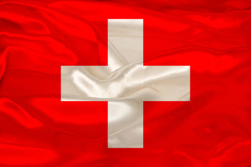 photo of beautiful colored national flag of modern state of Switzerland on textured fabric, concept of tourism, emigration, economy and politics, closeup