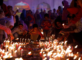 Sikh devotees light candles at a Sikh temple to mark the 550th birth anniversary of Guru Nanak Dev, the first Sikh Guru and founder of Sikh faith, in New Delhi
