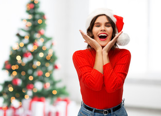 winter holidays and emotions concept - happy smiling young woman in santa helper hat over christmas...
