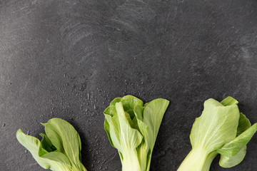 vegetable, food and culinary concept - close up of bok choy chinese cabbage on slate stone...