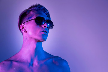 Handsome pumped up guy in black sunglasses. Sports guy, attractive male body. Studio shooting with color filters