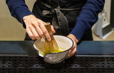 Female barista hands preparing matcha tea on a bowl, mixing it with a bamboo whisk in Busan, Korea.
