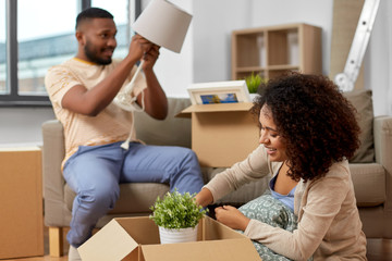 moving, people, repair and real estate concept - happy african american couple with photo frame and cardboard boxes sitting on sofa at new home