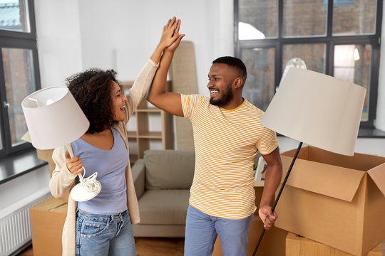 moving, people, repair and real estate concept - happy african american couple with lamps packing stuff into cardboard boxes at home and making high five