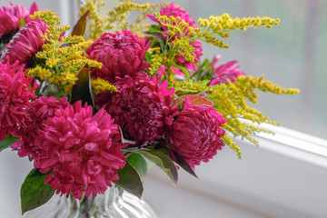Cadres-photo bureau Dahlia Bouquet of magenta dahlias. Fresh bunch purple pink with yellow peonies roses flower in glass vase on the window sill, white background. Autumn time concept. Still life, rustic style.