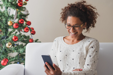 Cheerful woman holding mobile phone on christmas holiday
