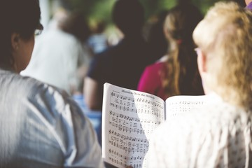 Selective focus shot from behind of people reading notes in the choir with a blurred background