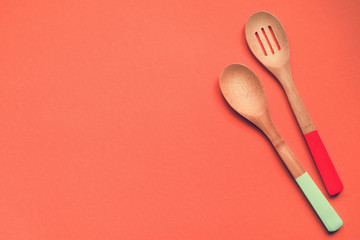 Two wooden spoons on a beige background, top view, copy space