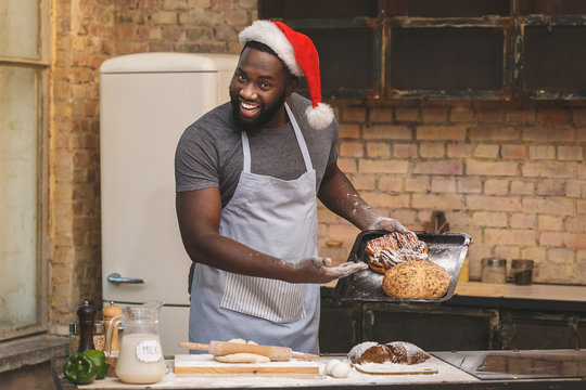 Christmas baking process. Chef wears apron, prepares dough for making loaf, uses different ingredients, in kitchen. Talented African American cook.