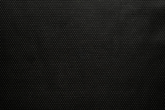 The background dense black modern durable fabric with a pronounced texture pattern