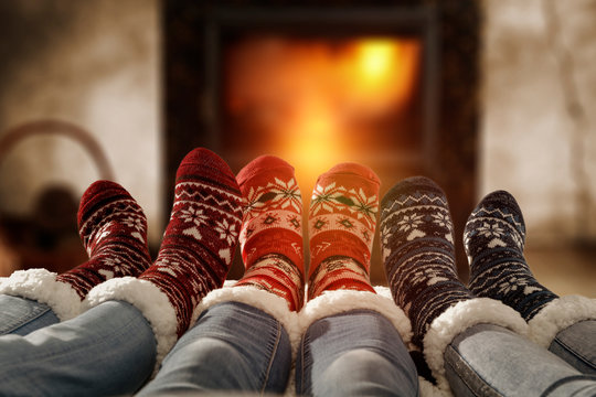 Woman legs in home interior with fireplace.Woolen socks and jeans.Free space for your decoration.Christmas cold winter night.Copy space.