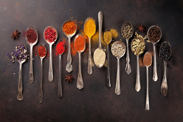 Various spices spoons on stone table Fototapete