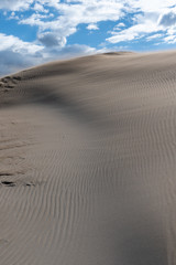 Sand forming dunes in the middle of the desert with a sky with clouds. Brown, blue and gray colors
