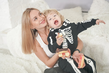 Mother and son child having fun with tasty sweet donuts indoors. Boy in halloween skeleton costume playing with lovely mom. Wall mural