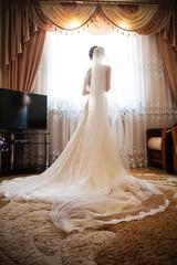 Beautiful bride in white wedding dress standing in her bedroom near window