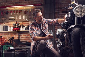 Man polish motorcycle in garage