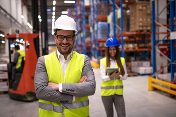 Portrait of successful warehouse worker or supervisor with crossed arms standing in large storage distribution area with forklift operating and female coworker taking notes in background. Wall mural