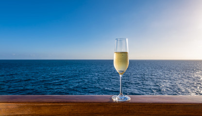 One single glass of sparkling white wine on wooden railing of cruise ship. Sea in the background. Clear blue sky. Alcoholic drink on summer vacation.
