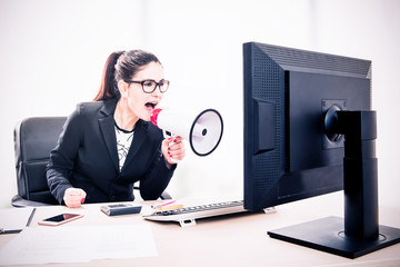 Businesswoman yelling through a megaphone sitting in the office