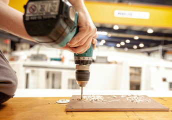 Close up of man drilling wood with a drill machine in a workshop