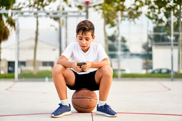 Kid  using  his mobile in a street basketball  court