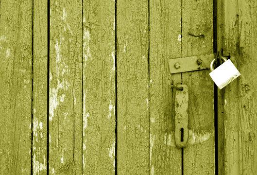 Grungy wooden door with lock in yellow tone.