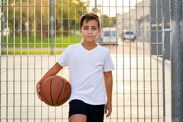 Kid with green eyes  playing basketball alone  in a street