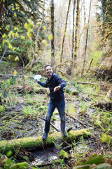 Man throws frisbee in forest while balancing on fallen tree.