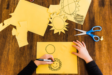 Young boy drawing and cutting out yellow sun
