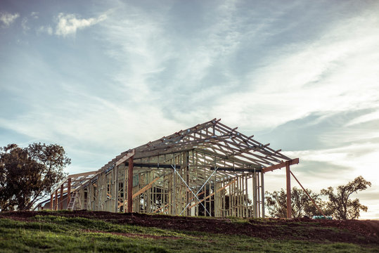 House frame on construction site stands on hill as farm gets build