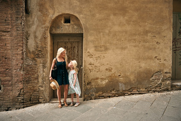 Mother and daughter standing by old house