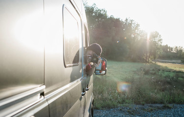 woman leaning out of a camper van taking a picture with a dslr