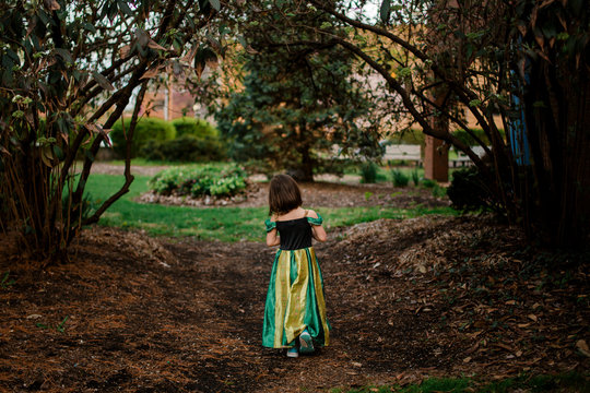 A little girl in a princess costume walks alone on a wooded path