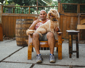 A happy man sits with glass of bourbon and dog on lap on wooden chair