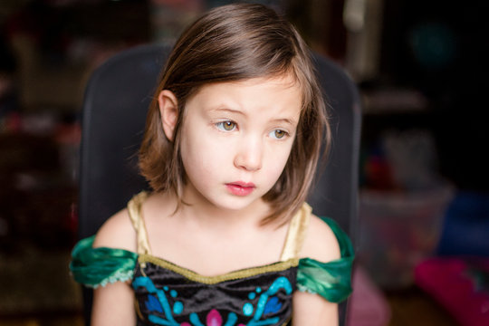 A little girl in a princess costume sits thoughtfully in a chair