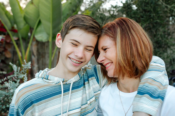 Smiling mom and teen son hugging with large plants in background