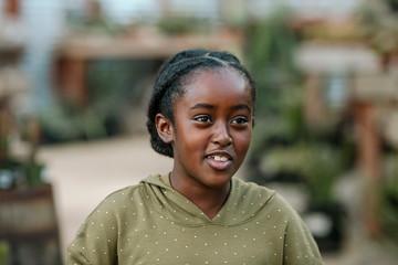 Beautiful smiling black girl with braids wearing a green shirt