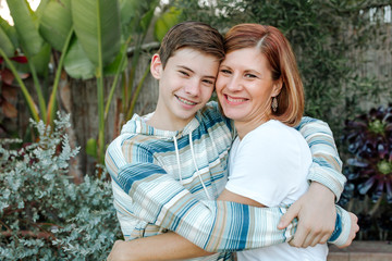 Smiling mom and teen son hugging outdoors with lush plants