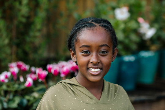 Beautiful smiling black girl in polka-dot shirt with flowers & plants