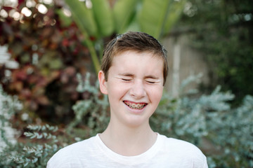 Laughing preteen boy with short hair and braces near lush plants