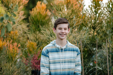Smiling teen boy with braces in blue striped hoodie outdoors