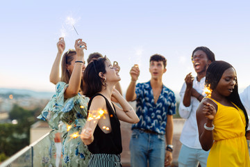 Group of happy multi-ethnic friends celebrating a party in the evening, holding sparklers