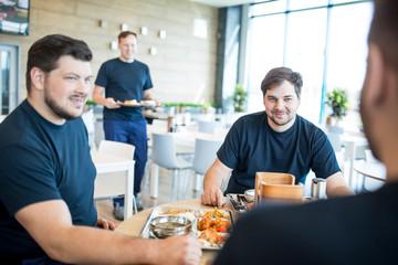Colleagues having lunch break in canteen