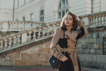 Outdoor autumn fashion portrait of young elegant woman wearing beige black trench coat, beret, with small patent faux leather shoulder bag, walking in street of city. Copy, empty space for text Wall mural