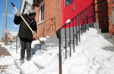 Sherry Strickland shovels snow from the steps of a church in Detroit, Michigan,