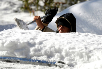 A man cleans the snow from the top of his vehicle in Detroit, Michigan,