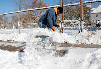 Kevin Strickland shovels snow from a sidewalk in Detroit, Michigan,